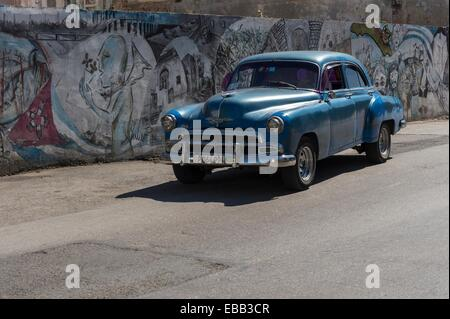 Cuban classic car seen pulling away from a graffiti strewn wall in a central Havana street, Cuba - Stock Photo