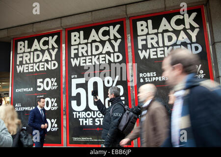 London, UK. 28 Nov 2014 - Black Friday Sales in London UK, Reporting in front of sign from Oxford Street Credit: - Stock Photo