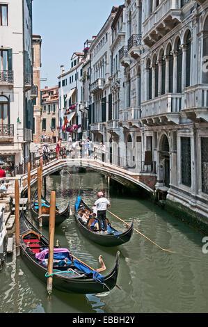 Bridge over canal Rio de la Canonica and gondalas with godalier and sunshine Venice Italy - Stock Photo