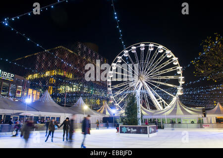 People skating on the ice rink in front of the library, Centenary Square, Birmingham, England. - Stock Photo