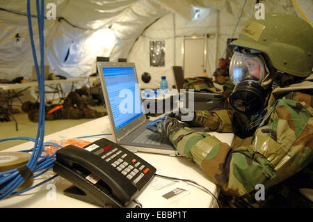 DAVIS-MONTHAN AIR FORCE BASE, Ariz. (AFPN) -- Staff Sgt. Tamara Needle checks her e-mail in Mopp 4 gear during exercise - Stock Photo