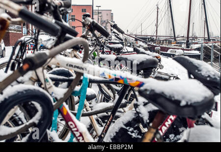 Bicycles covered with snow, ships masts in background - Stock Photo