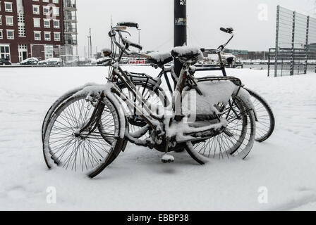 parked bicycles in snow against lantern pole - Stock Photo