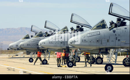 Four A-10 Thunderbolt IIs sit on the end of the runway as maintainers perform pre-flight inspections at Davis-Monthan - Stock Photo