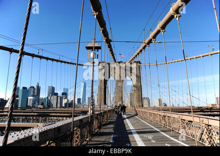 Manhattan New York USA November 2014  - Tourists crossing on Brooklyn Bridge looking back toward Manhattan Financial - Stock Photo