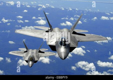 Two Air Education Training (AET) F-22 Raptor from Tyndall Air Force Base, fly in trail behind a KC-135R Stratotanker - Stock Photo