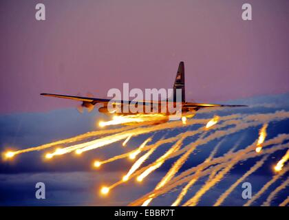 A C-130 from the Niagara Falls Air Reserve Station launches flares over Lake Ontario during a training exercise - Stock Photo