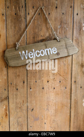 Welcome sign hanging from a nail on an old rustic wooden oak weathered front door. - Stock Photo