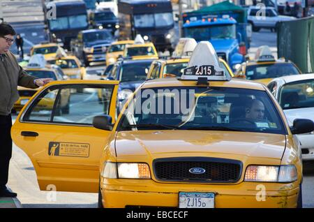 Taxicab letting off passengers in busy New York City - Stock Photo