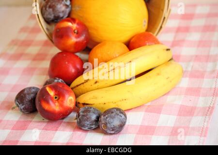 Fruit in a basket  Fruit in basket on its side  Melon surrounded with nectarines and some plums are inside the basket - Stock Photo