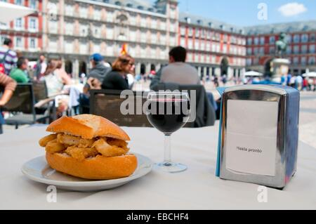 Fried squids sandwich with glass of red wine on a terrace. Main Square, Madrid, Spain. - Stock Photo