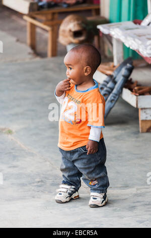 Local African toddler, a young boy, standing in a street in Antananarivo, or Tana, capital city of Madagascar - Stock Photo