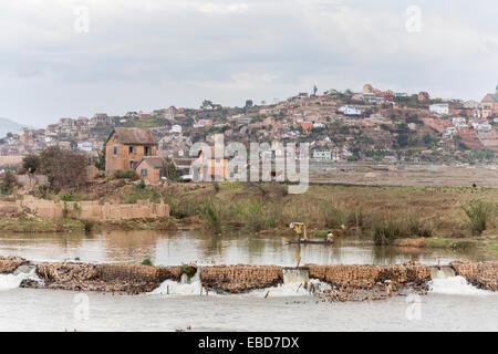Local lifestyle: Lake with brick dam for local fishermen and suburban shanty town scene at Antananarivo, or Tana, - Stock Photo
