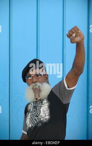 Senior man in the historic centre of Havana,with Cuban cigar in the mouth and wearing a black beret,in Cuba - Stock Photo