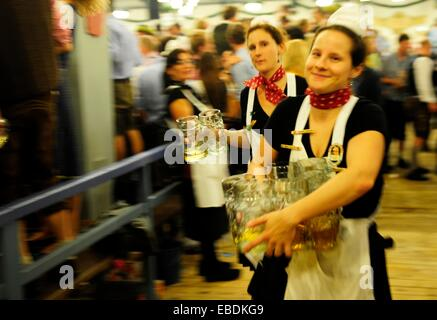 Females waiters with beer steins during Oktoberfest festival in Munich, Germany - Stock Photo