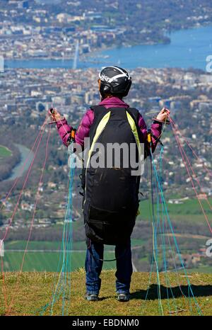woman waiting for wind, ready for taking off the paraglider from Mont Saleve in France, panorama of Geneva and Geneva - Stock Photo