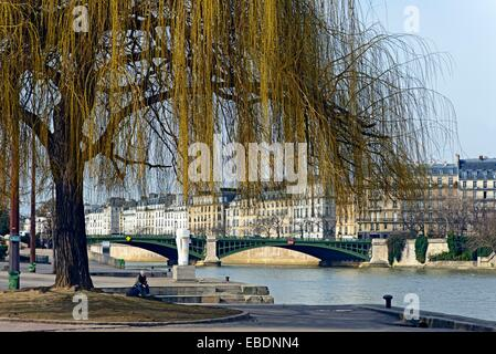 single man sitting, resting at promenade in Jardin Tino-Rossi, Gardens Tino-Rossi, Seine river banks, listed as - Stock Photo