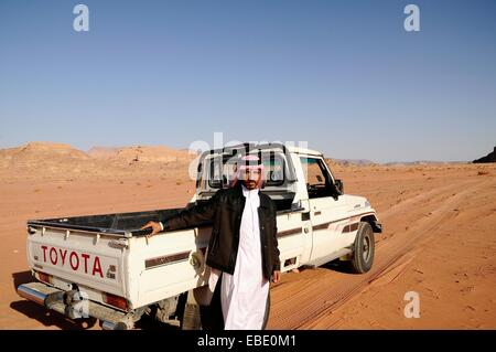 A beduin man with his 4x4 car Wadi Rum desert Jordan Middle East. - Stock Photo