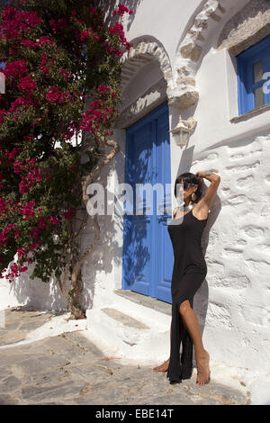 Woman posing in front of a house door, Amorgos, Cyclades Islands, Greek Islands, Greece, Europe. - Stock Photo