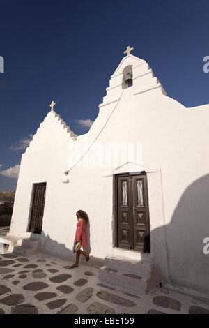 Woman posing in front of the Paraportiani Church Mykonos Cyclades Islands Greek Islands Greece Europe. - Stock Photo