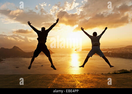Teenagers doing Star Jumps at Sunset overlooking Rio de Janeiro, Brazil - Stock Photo