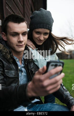 Close-up of young man and teenage girl outdoors, looking at cell phone, Germany - Stock Photo