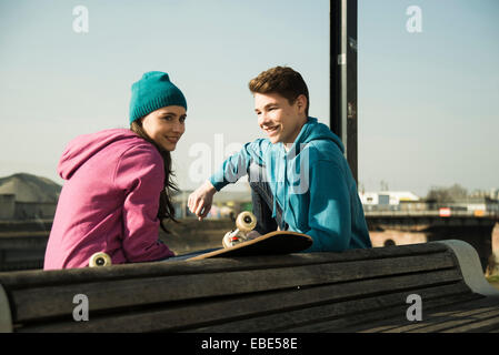 Teenage boy and girl sitting on bench outdoors with skateboard, industrial area, Mannheim, Germany - Stock Photo