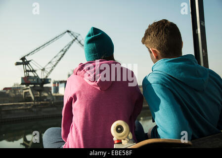 Backview of teenage girl and boy sitting on bench outdoors with skateboard, industrial area, Mannheim, Germany - Stock Photo