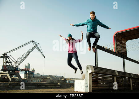 Teenage girl and boy jumping over bench outdoors, industrial area, Mannheim, Germany - Stock Photo