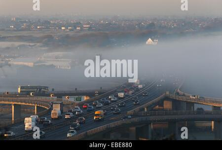 Motorist travel through the fog on a main road - Stock Photo