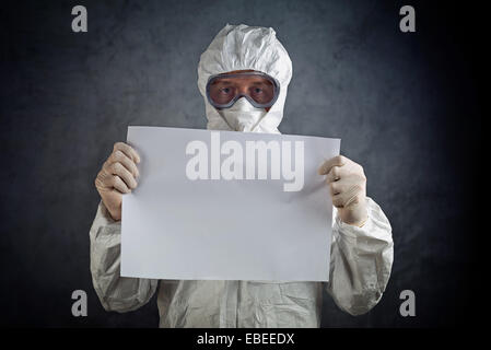 Medical healh care worker wearing protective gown, gloves, mask and goggles and holding blank paper as copy space. - Stock Photo