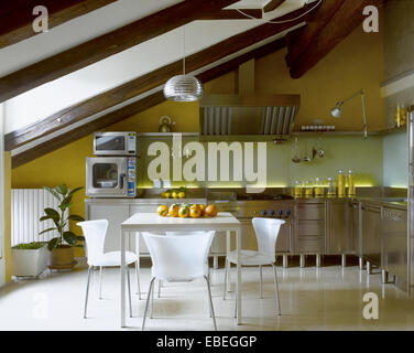 interior view of a modern kitchen in the attic room with dining table - Stock Photo