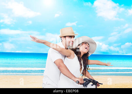 indian married couple goa beach Riding  Cycle - Stock Photo
