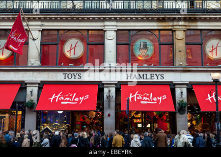 LONDON, UK - NOVEMBER 29TH 2014: Crowds of shoppers flood past and into Hamleys Toy Shop on Regent Street in London, - Stock Photo