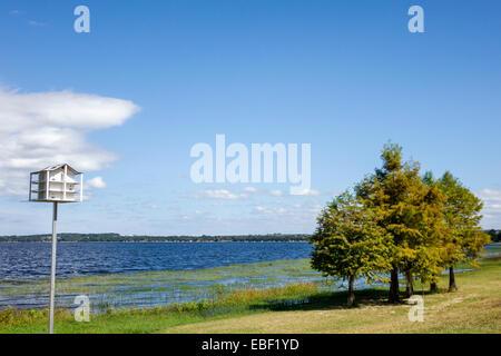 Clermont Florida Waterfront Park public Lake Minneola South Lake Trail path water birdhouse cypress trees - Stock Photo