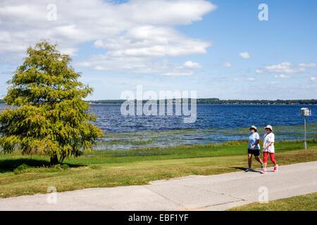 Clermont Florida Waterfront Park public Lake Minneola South Lake Trail path water birdhouse cypress trees woman - Stock Photo