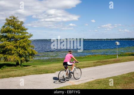 Clermont Florida Waterfront Park public Lake Minneola South Lake Trail path water woman bicycle riding - Stock Photo