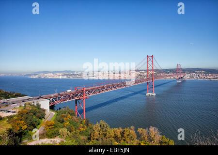 25 de Abril Bridge (Ponte 25 de Abril, 25th of April Bridge) over the Tagus river, connecting Almada and Lisbon - Stock Photo