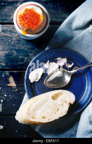 Breakfast with soft-boiled egg with red caviar in white eggcup, served with bread over old wooden table. Focus on - Stock Photo