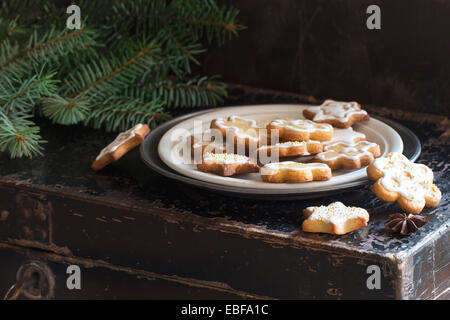 Christmas cookies on old black chest with Christmas tree - Stock Photo