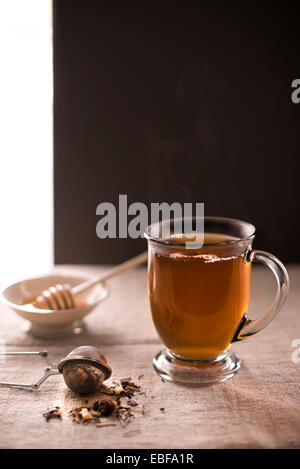 Steaming cup of hot tea with loose leaf tea in foreground and honey with dipper in background. Rustic, linen surface. - Stock Photo