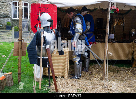 Two men dressed in medieval knight costumes shopping at market stall at the Ludlow Castle Christmas food and craft - Stock Photo