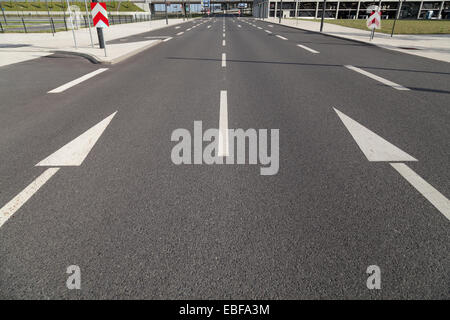 two arrows on asphalt by day - Stock Photo