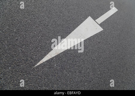 arrow in one direction on asphalt - Stock Photo