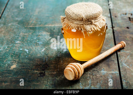 Honey jar and dipper on wooden background - Stock Photo