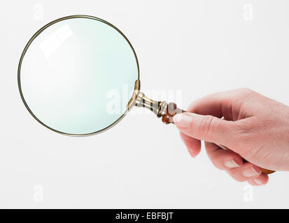 Woman hand holding magnifying glass isolated on white background - Stock Photo