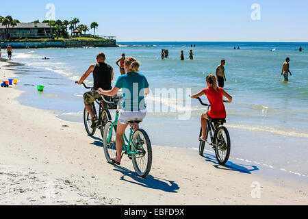 A familt riding beach cruiser bicycles along Crescent beach on Siesta Key Island in Sarasota FL - Stock Photo