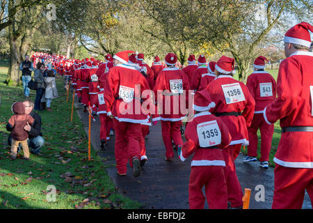 Rear view of people (men, women & children) dressed in red & white Father Christmas outfits walking, jogging, running - Stock Photo