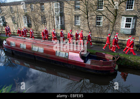People (men, women & children) dressed in red & white Father Christmas outfits are walking, jogging, running past - Stock Photo