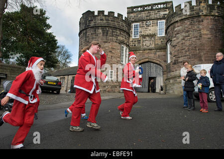 People (women & children) dressed in red & white Father Christmas outfits are walking, jogging, running & taking - Stock Photo